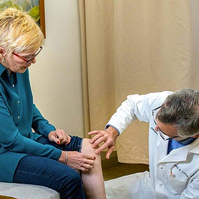 orthopedist examinging patinet's knee